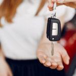 на изображении девушка берет ключи за проданый автомобиль